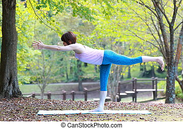Japanese woman outside doing yoga Warrior III Pose