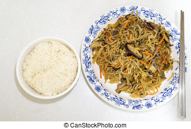 japchae with rice bowl - traditional korean dish called...