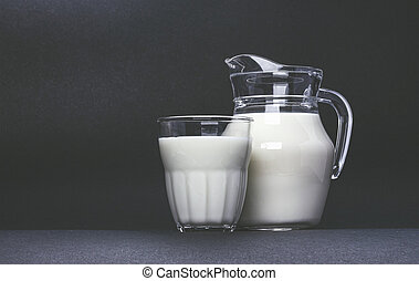 Jar and glass cup of milk on black background