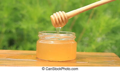 Jar and honey stick on the wooden table