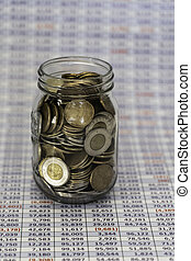 Jar full of coins with Spreadsheet in bavckground