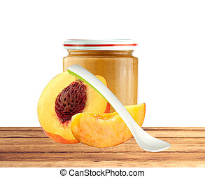 Jar of baby puree, spoon and peach slice on wooden table over white