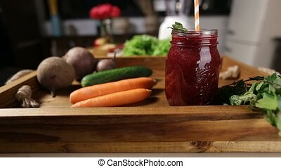 Jar of fresh beet smoothie with vegetables in tray - Mason...