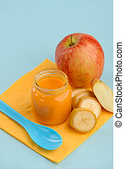 Jar of fruit puree, spoon and napkin on blue background