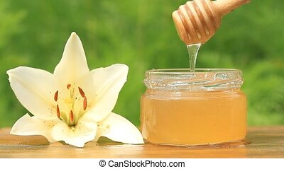 Jar of honey and lily flower