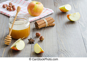 Jar of honey, honey stick, cinnamon, hazelnuts and apple