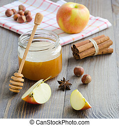 Jar of honey, honey stick, cinnamon, hazelnuts and red apple
