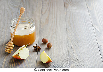 Jar of honey with honey stick, slices of apple, hazelnuts and anise