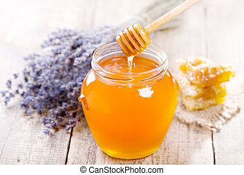 jar of honey with honeycomb and lavander flowers on wooden...