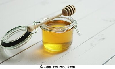 Jar of honey with spindle - Glass jar full of honey with...