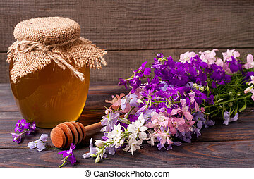 Jar of honey with wildflowers on a dark wooden background