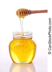 Jar of honey with wooden drizzler on white background