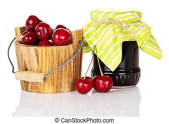 Jar of jam a wooden bucket with sweet cherries