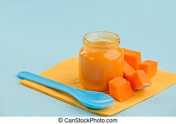 Jar of pumpkin puree and slices on blue background