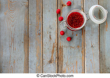 Jar of raspberry jam on the wooden table