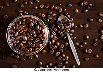 Jar of roasted coffee beans on wooden table with spoon.