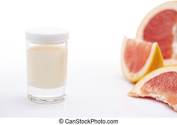Jar with candle cream and sliced grapefruit on a white background.