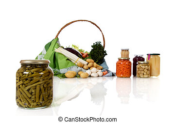 Jar with canned green beans, canned and fresh vegetables