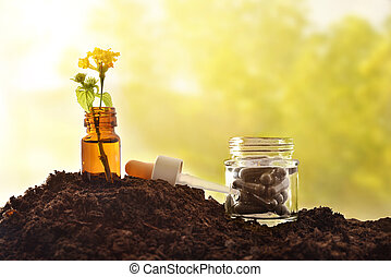 Jar with plant and capsules on soil and nature background