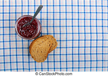 jar with raspberry jam and sliced bread on blue tablecloth