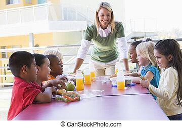 jardín de la infancia, profesor, supervisar, niños comer, almuerzo