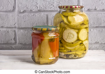 Jars of canned vegetables on a wooden background against a gray wall. Homemade vegetables for the winter