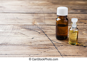 Jars of essential oils on a wooden background with copy space.