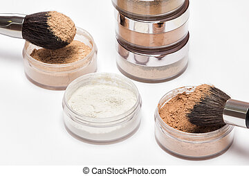 Jars of loose cosmetic powder with makeup brushes