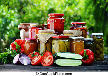 Jars of pickled vegetables in the garden. Marinated food.