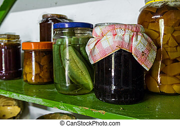 Jars of preserve are on the shelf in pantry. - Food staples...