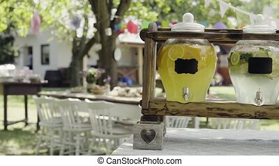 Jars with a tap on a wooden stand in a garden. - Soft drinks...