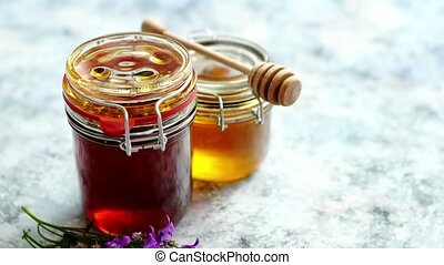 Jars with different kinds of fresh organic honey placed in a...