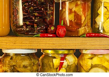 Jars with marinated food and organic raw vegetables. Preserved vegetables on wooden background. Various marinaded food. Life on a rural farm.
