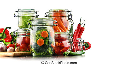 Jars with marinated food and raw vegetables isolated on white