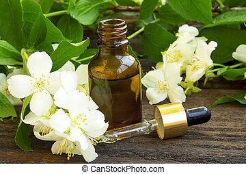 spa jasmine essence bottle with jasmine flowers and leaves near