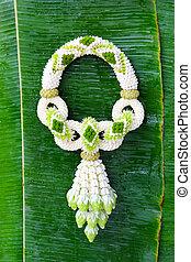 Jasmine garland of flowers on banana leaf background