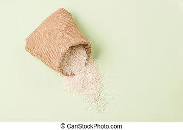 Jasmine white rice in sack on green background.