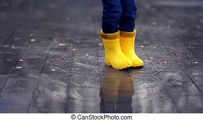 jaune, flaque, enfant, danse, heureux, bottes, jambes, caoutchouc, saut, petit
