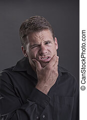 Jaw ache - Caucasian man wearing black shirt holds his lower...