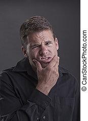 Jaw ache - Caucasian man wearing black shirt holds his lower...