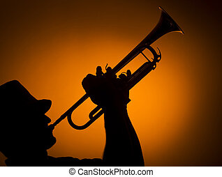 jazz - backlight musician playing trumpet on orange...
