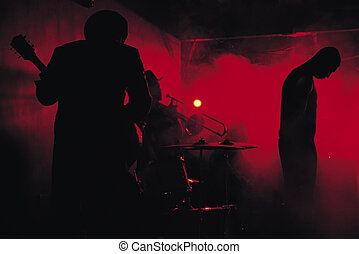 A jazz band shot in silhouette while performing in a club