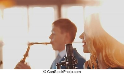 Jazz duet on stage of restaurant. Vocalist at microphone. Saxophonist. Style
