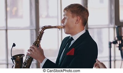 Jazz duet on stage. Saxophonist. Attractive vocalist at microphone. Music.