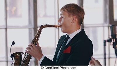 Jazz duet on stage. Saxophonist. Attractive vocalist at microphone. Music.