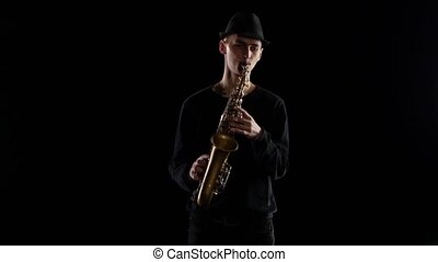 Jazz in the performance young musician saxophonist. Black background studio