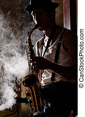 Jazz is his life. Handsome young jazz man playing sax with a...