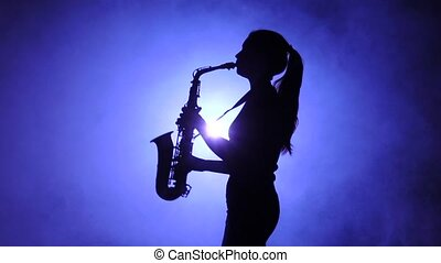 Jazz performed by musician girl playing saxophone. Silhouette, slow motion