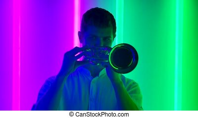 Jazz solo performance by a professional trumpeter. A man in a white shirt performs in a dark studio against the backdrop of bright neon lights. Musical show. Close up. Slow motion