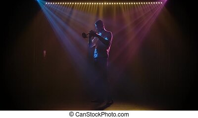 Jazz trumpet performance on a dark stage in the spotlight. Silhouette. Slow motion